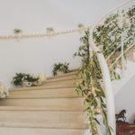 Guirlande lumineuse et végétale autour de la rampe d'un escalier