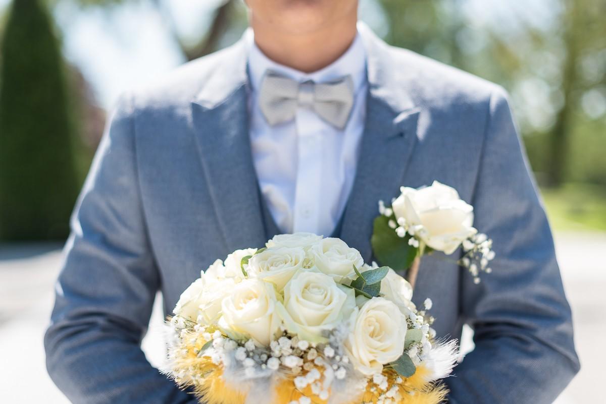 Le marié bleu et gris avec le bouquet